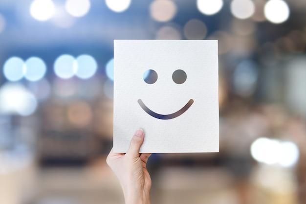 Mano che tiene carta bianca con emoticon faccina sorridente su sfondo bokeh chiaro.