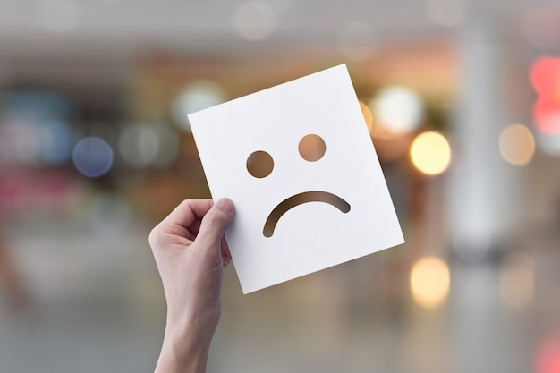 Mano che tiene carta bianca con emoticon faccia infelice su sfondo bokeh chiaro.