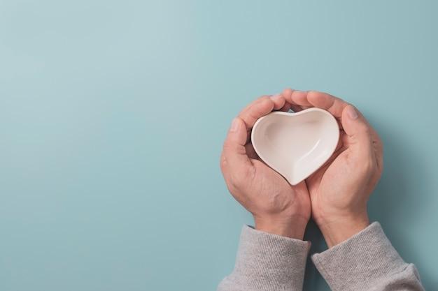 Mano che tiene la piccola ciotola bianca a forma di cuore e lo spazio della copia su sfondo blu per il concetto di san valentino