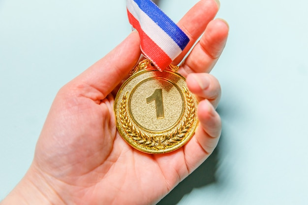 Mano che tiene la medaglia del trofeo d'oro vincitore o campione isolato su sfondo blu