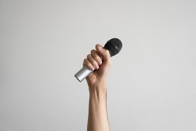 Mano che tiene un microfono wireless su sfondo bianco