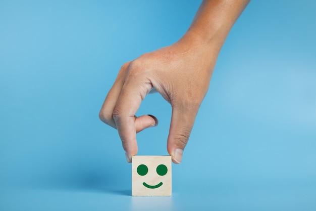 Mano che tiene il cubo di legno con l'icona faccina sorridente. valutazione del servizio clienti, concetto di indagine sulla soddisfazione.