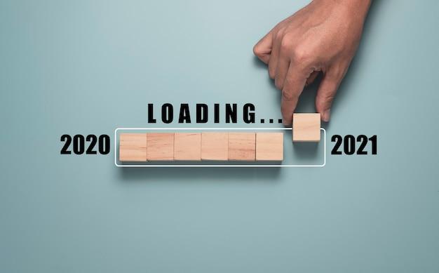 Mano che tiene il cubo di blocco di legno e messo giù per il conto alla rovescia 2020 e l'inizio dell'anno 2021