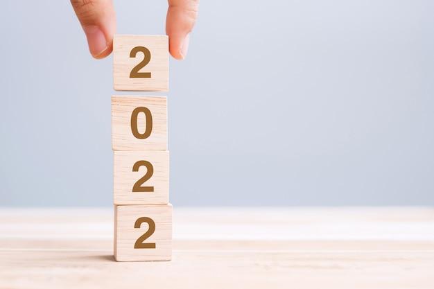Mano che tiene il blocco cubo di legno con testo 2022 sullo sfondo della tabella. concetti per la risoluzione, il piano, la revisione, l'obiettivo, l'inizio e le vacanze di capodanno