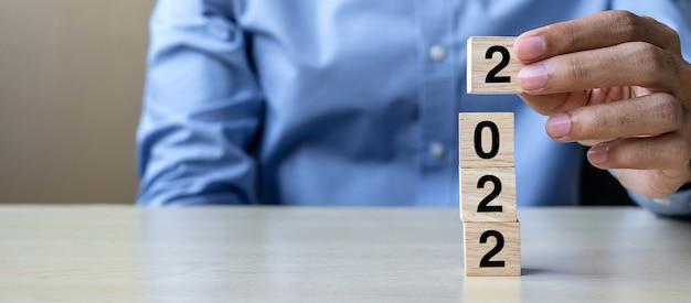 Mano che tiene blocchi di cubo di legno con testo 2022 sul tavolo Foto Premium