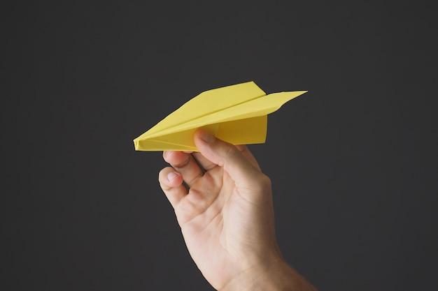 Mano che tiene aeroplano di carta giallo su sfondo grigio.