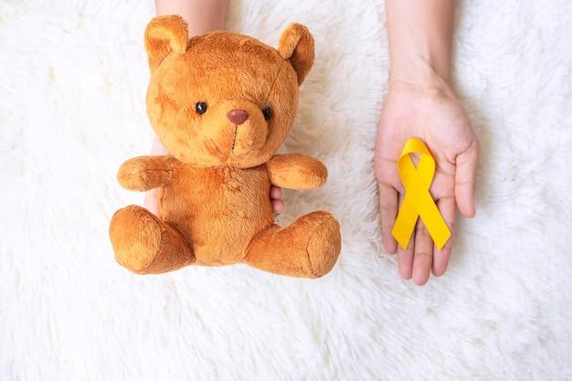 Mano che tiene il nastro giallo e la bambola dell'orso su sfondo bianco per sostenere la vita e la malattia dei bambini. settembre childhood cancer awareness month e concetto di giornata mondiale del cancro
