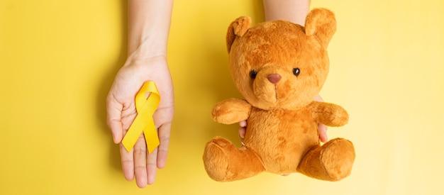 Mano che tiene il nastro giallo e la bambola dell'orso su sfondo giallo per sostenere la vita e la malattia dei bambini. settembre childhood cancer awareness month e concetto di giornata mondiale del cancro