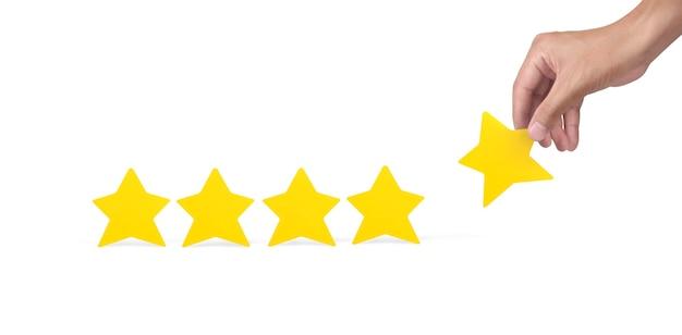 Mano che tiene una stella gialla. aumentare la valutazione della valutazione e il concetto di classificazione