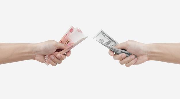 Mano che tiene le banconote in yuan e in dollari usa isolate su sfondo bianco cambio valuta