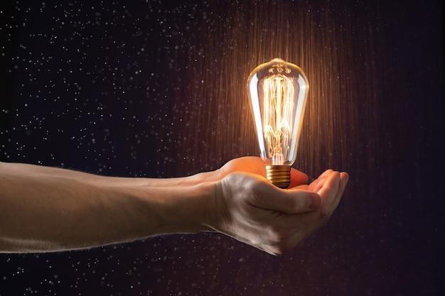 La mano tiene in aria una lampadina vintage senza fili