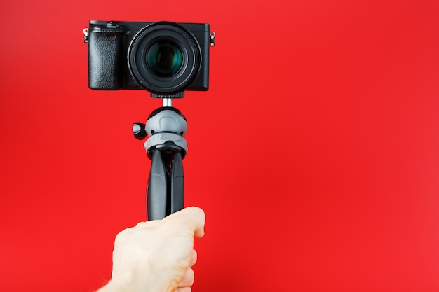 Una mano tiene una fotocamera reflex nera su un treppiede, isolata su uno sfondo rosso.