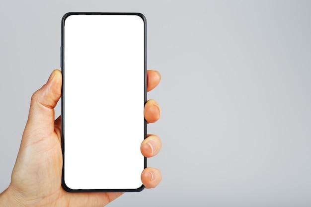 La mano tiene lo smartphone nero con schermo bianco vuoto e design moderno senza cornice isolato su superficie grigia