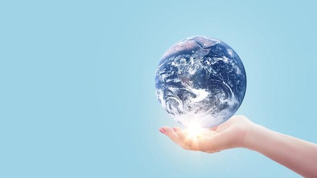 La mano tiene il pianeta terra blu con la luce del tramonto su colore blu pastello. salva il concetto di terra. idea creativa per l'ambiente