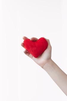 La mano tiene il cuore rosso brillante del giocattolo. concetto di amore, relazioni, salute, cura, medicina.