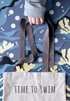 La mano tiene la borsa di tela con testo tempo di nuotare sull'acqua di mare blu astratta