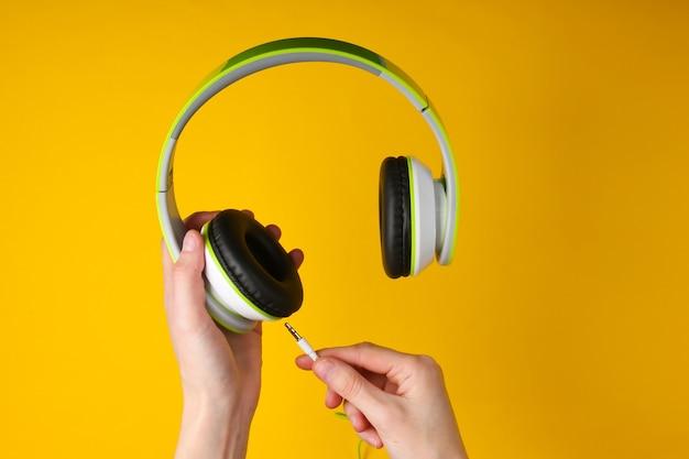 La mano tiene e collega un cavo alle cuffie stereo su una superficie gialla