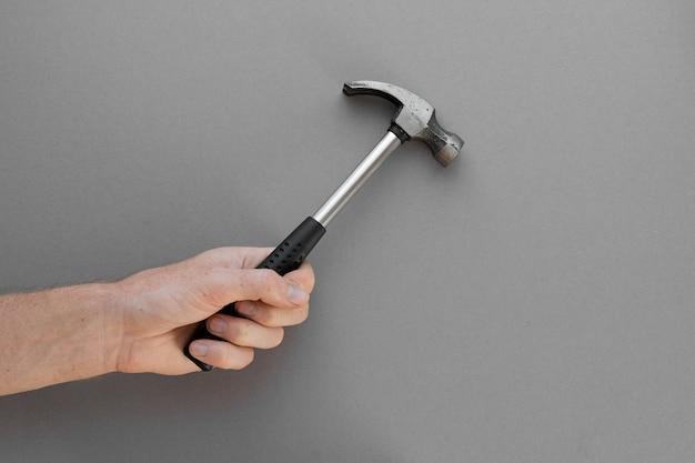 Una mano tiene un martello da costruzione su uno sfondo grigio