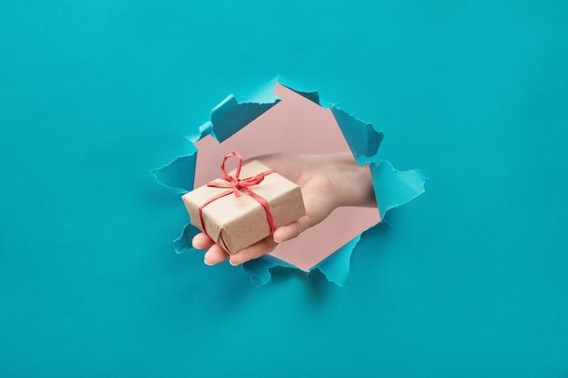 La mano tiene un regalo artigianale attraverso un foro di carta strappato