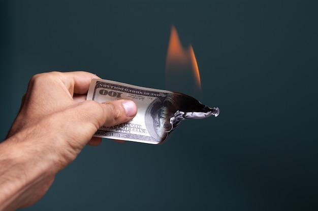 La mano tiene una banconota da un dollaro che sta bruciando
