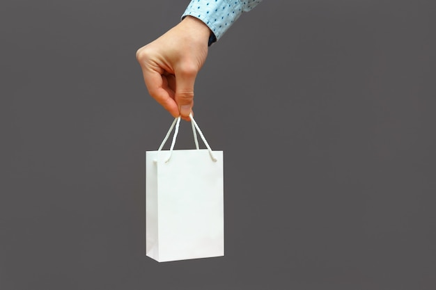 Una mano tiene un regalo in una borsa bianca su un muro grigio scuro
