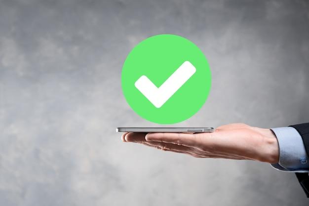 La mano tiene l'icona verde segno di spunta,segno di spunta, icona di spunta,segno di destra,pulsante di segno di spunta verde cerchio,fatto.su sfondo scuro.banner.spazio di copia.