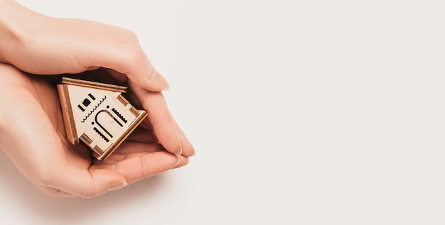 La mano tiene il modello in miniatura della casa su priorità bassa bianca. investimenti, immobili, casa, abitazioni