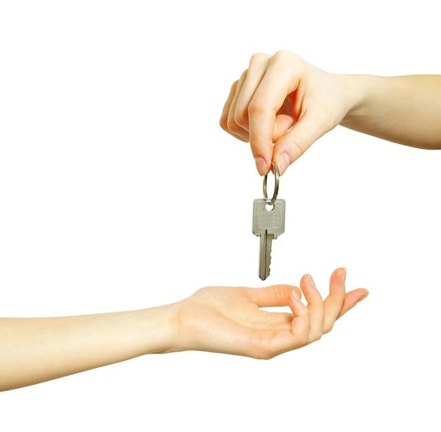 La mano tiene una chiave isolata su bianco