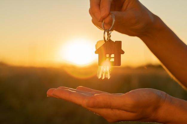 La mano tiene la chiave della nuova casa con un portachiavi a forma di casa sullo sfondo di ...