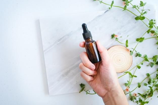 La mano tiene la cura della pelle naturale sul tavolo di marmo con fiori