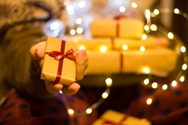 La mano tiene una confezione regalo. ragazza in un maglione lavorato a maglia tiene una pila di scatole regalo in ghirlanda luminosa