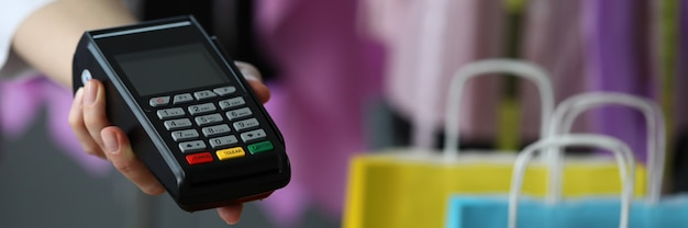La mano tiene il terminale per il pagamento con carta di credito