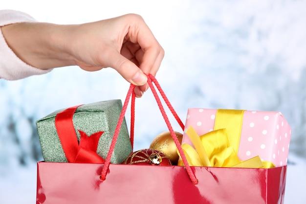 La mano tiene il pacchetto con le palle di capodanno e i regali sul muro di neve