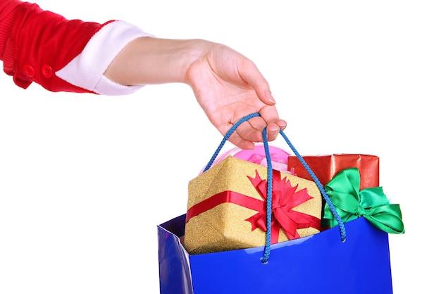 La mano tiene il pacchetto con i regali di capodanno isolati su bianco