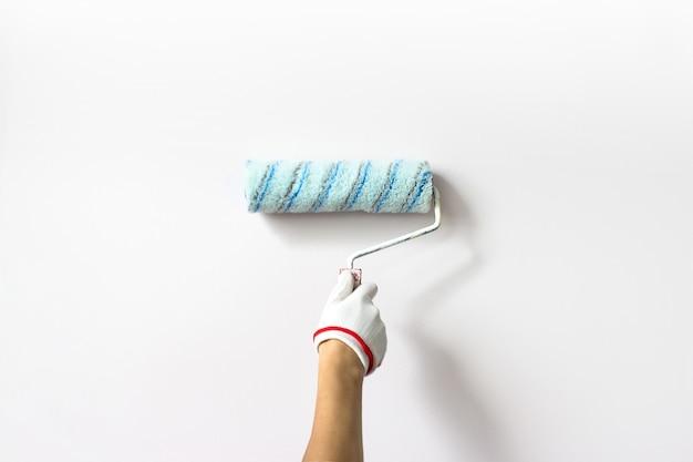 La mano tiene il rullo di vernice e dipinge un muro bianco. muro dipinto a mano del decoratore con rullo.