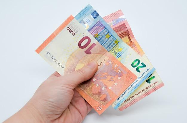 La mano tiene le banconote cartacee della valuta euro in tagli da 10 e 20