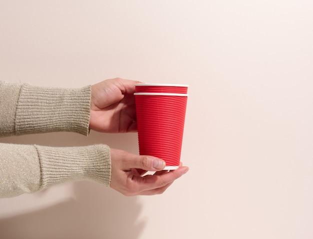 La mano tiene le tazze rosse del cartone di carta per caffè, fondo beige. stoviglie ecologiche, zero sprechi