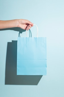 La mano tiene una borsa della spesa di carta su sfondo blu. ombre dure.