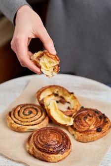 La mano tiene un pezzo di burro rotolare sul tavolo con panini con semi di papavero e uvetta. colpo verticale