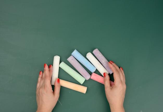 La mano tiene un pezzo di gesso bianco sullo sfondo di una lavagna verde vuota, concetto di presentazione, ritorno a scuola