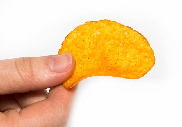La mano tiene le patatine fritte. isolato su uno sfondo bianco.