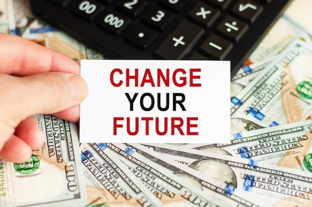 Una mano tiene un cartello con la scritta: cambia il tuo futuro sullo sfondo delle banconote e una calcolatrice sul tavolo