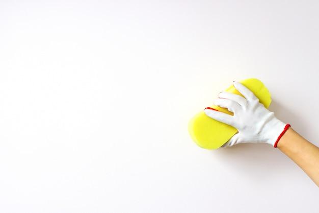 La mano tiene la spugna e lava un muro su uno sfondo bianco. pulizie o pulizie