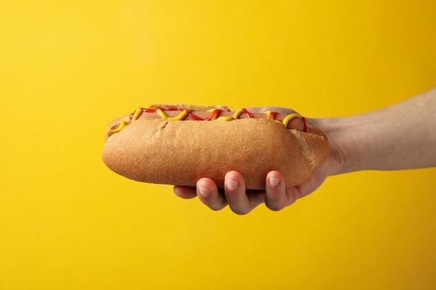 La mano tiene il hot dog saporito su superficie gialla