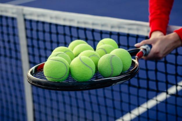 Una mano tiene una racchetta da tennis su cui giace una pallina gialla. palle da tennis e rucola sul campo di corte blu.