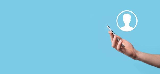 La mano tiene l'interfaccia dell'icona della persona dell'utente su sfondo blu. simbolo dell'utente per il design del tuo sito web, logo, app, ui.banner.