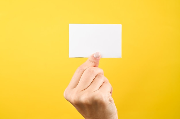 La mano tiene il segno in bianco bianco su sfondo giallo.