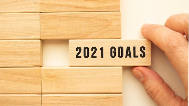La mano tiene un cubo di legno con il testo obiettivi 2021
