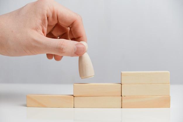 La mano tiene la figura di legno sulla scala di legno