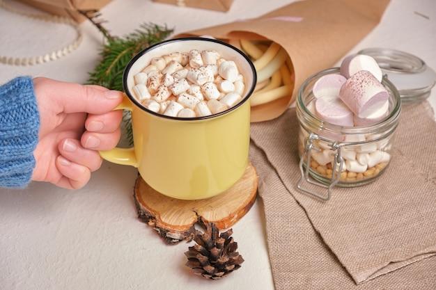 La mano tiene una tazza gialla con cocao e marshmallow